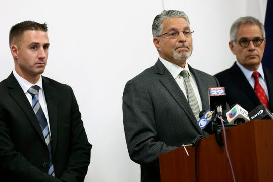 In this Tuesday, Sept. 3, 2019 photo, Anthony Voci, center, chief of the Philadelphia District Attorney's homicide unit, speaks during a news conference announcing the arrest of Theodore Dill Donahue as a suspect in the 1991 murder of Denise Sharon Kulb at the Pennsylvania State Police Troop K barracks in West Philadelphia. At left is Trooper Andrew Martin, who helped investigate the cold case, and at right is Philadelphia District Attorney Larry Krasner. ( Tim Tai/The Philadelphia Inquirer via AP) ORG XMIT: PAPHQ603