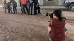MCALLEN, TX – Sandy Hooper takes pictures as migrants wait to be transported to a detention facility in Texas.
