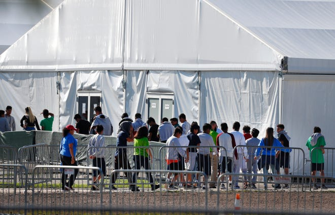 In this Feb. 19, 2019 file photo, children line up to enter a tent at the Homestead Temporary Shelter for Unaccompanied Children in Homestead, Fla.