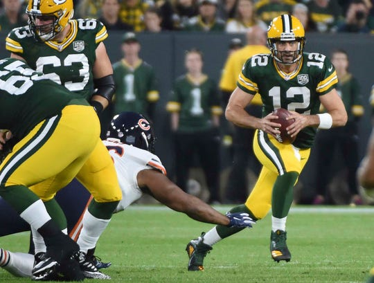Green Bay Packers quarterback Aaron Rodgers (12) scrambles in the first quarter during the game against the Chicago Bears at Lambeau Field.
