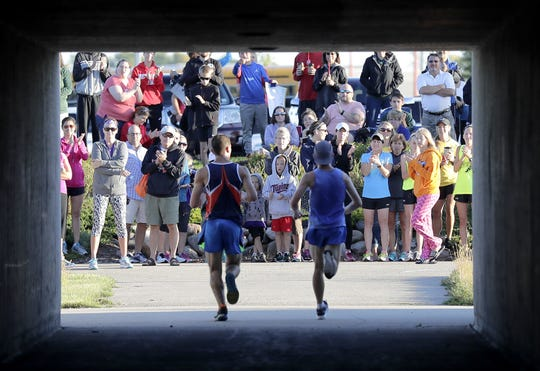 A crowd cheers as runners enter the CE Trail during the Fox Cities Marathon in 2016.