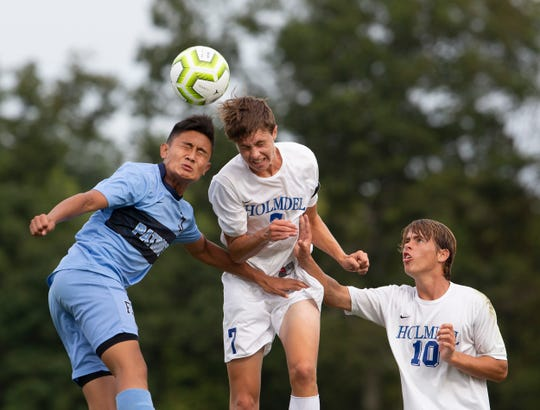 Freehold's Adam Havens and Holmdel's Eric Hinds battle for a headball as Holmdel's Connor Hinds looks on. Holmdel Boys Soccer vs Freehold Township in Freehold NJ on September 5, 2019.