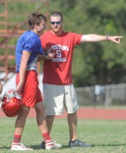 Sweetwater football coach Ben McGehee, right, delivers instructions to sophomore quarterback Leo Holsey during practice Wednesday at the Mustangs' practice field.