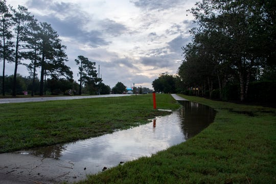 A dip in a sidewalk is flooded with water in Wilmington, North Carolina on the morning of Sept. 5, 2019. Hurricane Dorian is expected to arrive around 2 a.m. Friday.