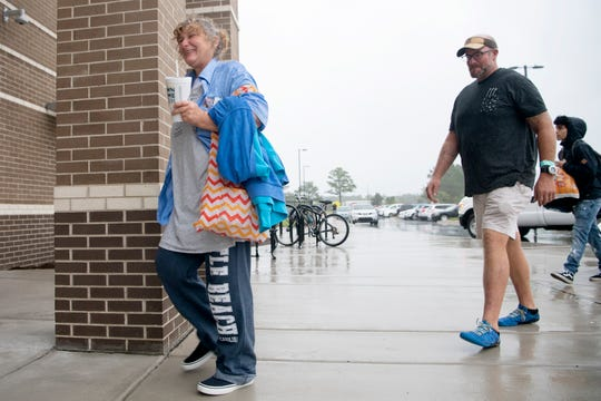 Pam Newnam and Matt Rollins enter the emergency shelter at Wrightsville Beach Elementary at John J. Blair School after leaving to grab fast food in Wilmington, North Carolina on Sept. 5, 2019. Newnam has been staying near the Greyhound Station which is closed because of Hurricane Dorian.