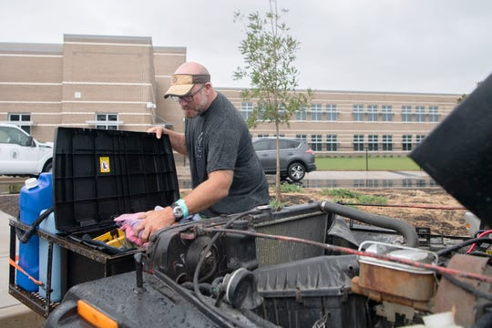 Matt Rollins searches for a tool to work on his jeep outside of the emergency shelter at Wrightsville Beach Elementary at John J. Blair School after leaving to grab fast food in Wilmington, North Carolina on Sept. 5, 2019. Rollins was hoping to make it to Virginia Beach where is originally from but the truck that he purchased wasn't available yet so he plans to stay at the shelter during Hurricane Dorian.