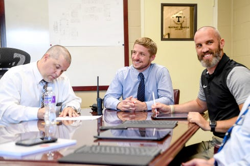 From left, Tuscola principal Todd Tratham, assistant principal Graham Haynes and Pisgah athletic director Casey Kruk have a meeting with fellow officials September 3, 2019, to discuss the rivalry game between the two schools.