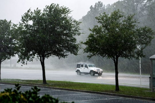 A Jeep drives past the New Hanover County Public Library through high winds and rain as a band of weather from Hurricane Dorian strikes Wilmington, North Carolina on Sept. 5, 2019.
