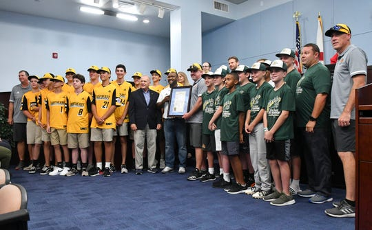 Brevard County commissioners stand with members of the Viera Suntree Juniors and Majors little league teams Thursday afternoon. Commissioners recognized the two teams for their performance in the Little League World Series