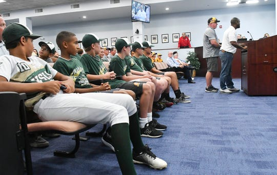 Viera Suntree Little League players watch as Juniors coach Jason Allen and Majors coach Russell Cheatham stand before Brevard County commissioners Thursday afternoon in Viera. Commissioners recognized the two teams for their performance in the Little League World Series this season.
