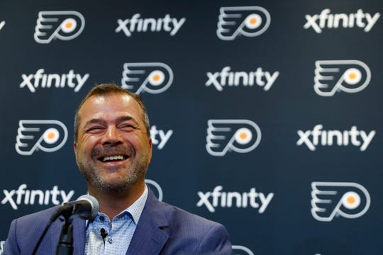 The Flyers' new coach has sat down with a handful of players each day since he came to town Sunday. Training camp starts next week.