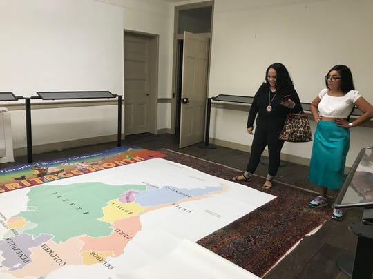 Beatrice Caraballo (left) and Shawnick Rodriguez look at a map of South and Central America that will hang in a new Latinx heritage exhibit at the Camden County Historical Society.