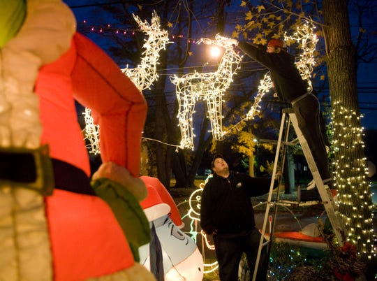 Michael Brown (left) of Cherry Hill and Rich Italiano, nephew of homeowner Frank Italiano, string Christmas lights on Mercer Street in Cherry Hill. The two-home display was part of a South Jersey tradition for more than 20 years.