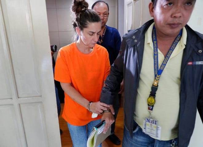 American Jennifer Erin Talbot from Ohio is escorted after a press conference by the National Bureau of Investigation (NBI) in Manila, Philippines on Thursday, Sept. 5, 2019. The NBI said that the 43-year-old Talbot was arrested at the Ninoy Aquino International Airport yesterday for trying to bring out of the country a 6-day old Filipino baby without proper travel documents. (AP Photo/Aaron Favila)