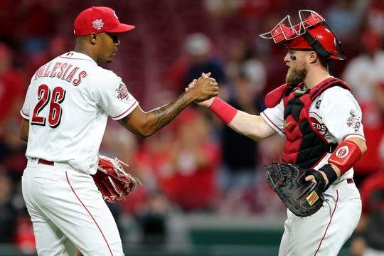 Cincinnati Reds relief pitcher Raisel Iglesias (26), left, and Cincinnati Reds catcher Tucker Barnhart (16), right, shake hands in the ninth inning of an MLB baseball game against the Philadelphia Phillies, Wednesday, Sept. 4, 2019, at Great American Ball Park in Cincinnati. The Cincinnati Reds won, 8-5