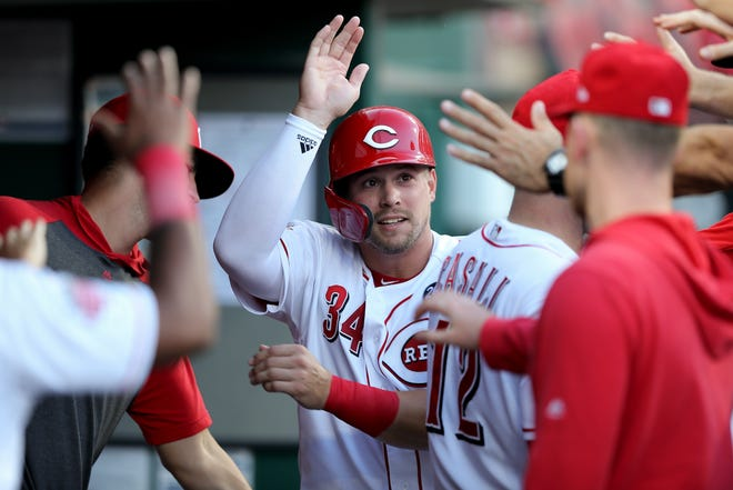 Former Cincinnati Reds left fielder Brian O'Grady (34) is congratulated in the dugout after scoring in the second inning against the Philadelphia Phillies at Great American Ball Park on Sept. 4, 2019.