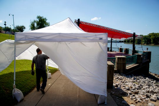 Rick Valles, production manager for Warbabies Productions, passes through a set up tent heading to one of the stages being built for Riverfest at McGregor Park in Clarksville, Tenn., on Thursday, Sept. 5, 2019.