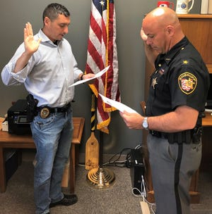 "Coshocton County Assistant Prosecutor Ben Hall is sworn in as a special deputy with the Tuscarawas County Sheriff's Office by Sheriff Orvis Campbell, as he recently completed the Ohio Peace Officer Training Academy at Zane State College. As a prosecutor working with the local sheriff's office, Hall said he ""gained an appreciation for what it takes to investigate a case and submit it for prosecution. I began to see the importance of a team approach, working together as opposed to two separate and distinct offices."""