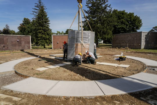 Workers install a center columbarium for the new Woodward Garden for Cremation at Roseland Park Cemetery in Berkley on Friday, Aug. 30, 2019. Truckloads of memorial and columbaria were delivered for the planned cremation garden to accommodate the growing trend of people choosing cremation over traditional burial.