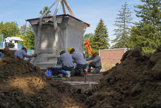 Workers install a columbarium for the new Woodward Garden for Cremation at Roseland Park Cemetery in Berkley.