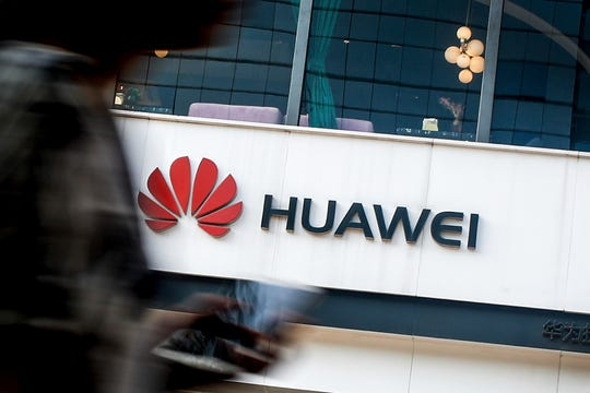 "FILE - In this July 30, 2019, file photo a woman walks by a Huawei retail store in Beijing. Chinese tech giant Huawei has accused U.S. authorities of trying to coerce employees to gather information on the company and of trying to break into its information systems. The company, the target of U.S. accusations that it is a security threat, said Wednesday, Sept. 4, that American officials were using ""unscrupulous means"" to disrupt its business."