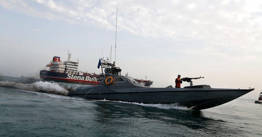 In this July 21, 2019 file photo, a speedboat of the Iran's Revolutionary Guard moves around a British-flagged oil tanker, the Stena Impero, which was seized by the Guard, in the Iranian port of Bandar Abbas.