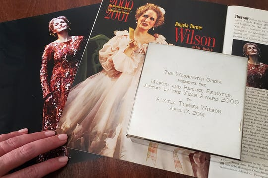 "Opera singer Angela Turner Wilson displays her 2000 Artist of the Year award from the Washington Opera next to a photo of herself from a 1999 performance of ""Le Cid,"" left, and a magazine article in a Washington Opera magazine, at her home in Texas."