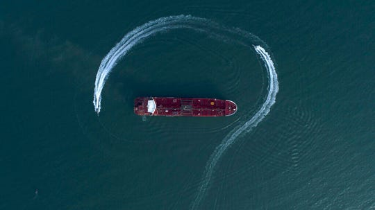 In this July 21, 2019 file photo, an aerial view shows a speedboat of Iran's Revolutionary Guard moving around the British-flagged oil tanker Stena Impero, which was seized in the Strait of Hormuz by the Guard, in the Iranian port of Bandar Abbas.