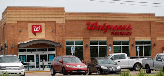 Customers drive through a Walgreens parking lot in Jackson, Miss., in this Tuesday, June 25, 2019, file photo. Walgreens asked gun owners to leave their firearms outside the store going forward, joining a number of large retailers who have in recent days said that open-carry firearms are no longer welcome at their locations.