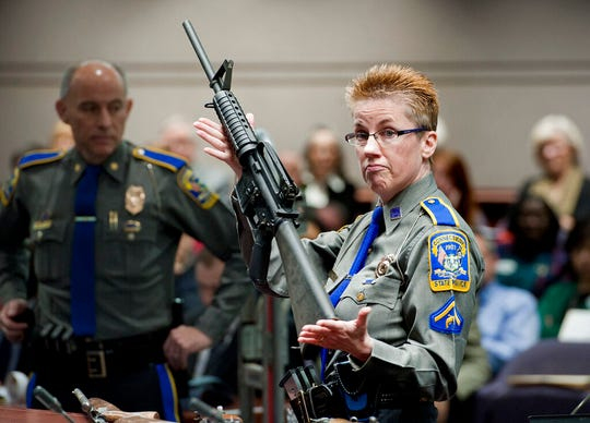 In this Jan. 28, 2013, file photo, firearms training unit Det. Barbara J. Mattson, of the Connecticut State Police, holds up a Bushmaster AR-15 rifle, the same make and model of gun used by Adam Lanza in the Sandy Hook School shooting, for a demonstration during a hearing of a legislative subcommittee reviewing gun laws, at the Legislative Office Building in Hartford, Conn. Ten states and nearly two dozen members of Congress are joining the National Rifle Association in supporting gun-maker Remington Arms as it fights a Connecticut court ruling involving the Sandy Hook Elementary School shooting.