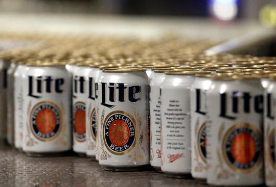 """FILE - In this March 11, 2015 file photo, newly-filled and sealed cans of Miller Lite beer move along on a conveyor belt, at the MillerCoors Brewery, in Golden, Colo. A federal judge has ordered Anheuser-Busch to stop using packaging that implies MillerCoors' light beers contain corn syrup. U.S. District Judge William Conley granted a preliminary injunction sought by MillerCoors. Bud Light's packaging says """"No Corn Syrup"""" in bold letters."""