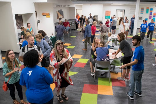 People fill the Bronstien lobby in the new Ascension St. Vincent YMCA in Downtown Evansville during the grand opening Thursday evening, Sept. 5, 2019.