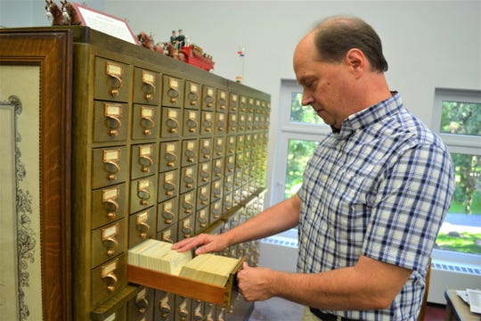 John Ransom, the head librarian at the Rutherford B. Hayes Presidential Library, looks through a vintage card catalogue where information about President Hayes' correspondence is stored.