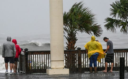 A group of people watch waves crash on the shore from Hurricane Dorian around high tide in Myrtle Beach, South Carolina Thursday, Septemeber 5, 2019.