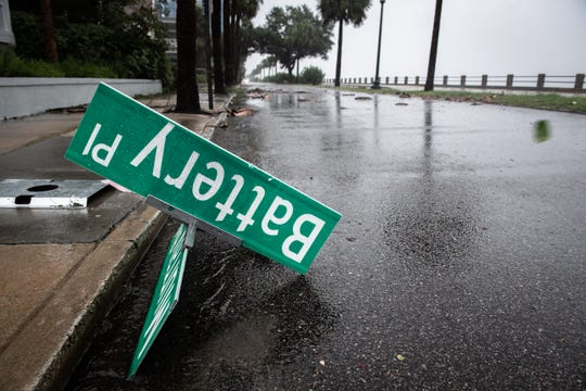 A street sign lies on the road on Murray Boulevard on the Battery in Charleston, SC during Hurricane Dorian Thursday, September 5, 2019. The storm center was 80 miles south-southeast of Charleston at 7 a.m. packing sustained winds of 115 mph, according to the National Hurricane Center.