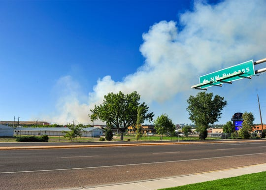 A large grass fire burns on Hill 57, Wednesday afternoon.