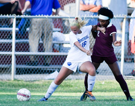 Memorial's Adelyn Holt (16) holds off Henderson County's Nadia Gilbert (2) as the Memorial Tigers play the Henderson County Lady Colonels at Colonel Field in Henderson Wednesday evening September 4, 2019.