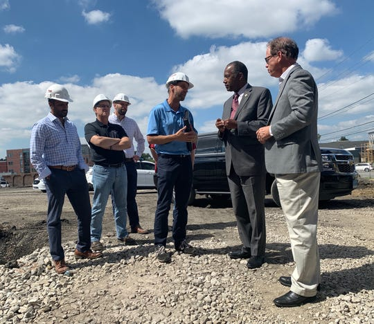 U.S. Housing and Urban Development Secretary Ben Carson (second from right) and Sen. Mike Braun (far right) speak with developers at the P.R.  Mallory site in Indianapolis .