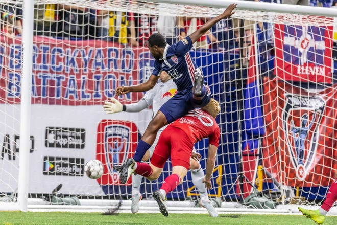 Indy Eleven forward Dane Kelly climbs over New York Red Bulls II midfielder Sean McSherry to head home the 83rd minute game-winner at Lucas Oil Stadium.