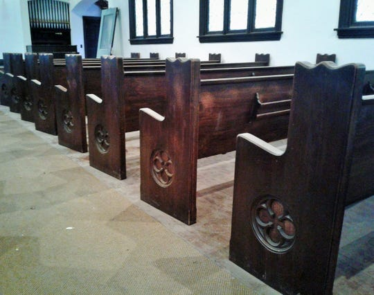 These antique church pews in the empty First Unitarian Church in Iowa City are being offered to the public for free by the local developer of this property, Jesse Allen.