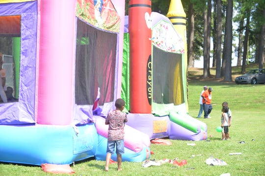 Kids play on the two bounce houses during the Lincoln Courts Legacy Reunion picnic Saturday at Forest Hill Park.