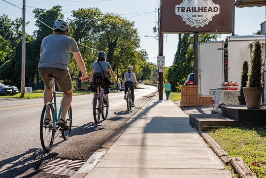 Cyclists ride by Trailhead, one of the many community sponsors of the Pedal Jam Knoxville event coming up on Sept. 28.