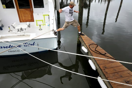 Brian Taylor, captain and owner of the fishing charter boat Carolina Girl, leaps from the boat to the docks in Hatteras Village after setting the boat's lines on Wednesday, Sept. 4, 2019 to handle the possible high winds, flooding and severe tides that could come from Hurricane Dorian.