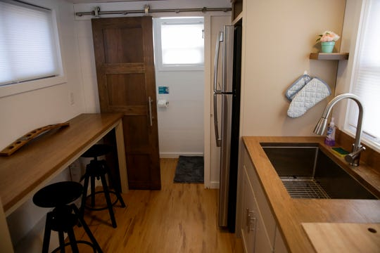 The kitchen area and bathroom inside one of the eight tiny homes at Hammer Down Town, Thursday, Sept. 5, 2019 in West Lafayette. The tiny home community from Try It Tiny, located at the corner of 3rd st. and McCutcheon drive, has eight homes available for booking for six home games this season.