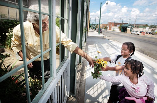 August 11, 2014 - Nick Vergos cuts flowers from a garden at the Rendezvous shipping facility in the Pinch District for Juzthize Clark, 7, and his sister Journei Clark, 4, as they head home from school.