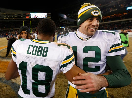 Green Bay Packers quarterback Aaron Rodgers (12) celebrates with wide receiver Randall Cobb (18) after an NFL football game against the Chicago Bears, Sunday, Dec. 29, 2013, in Chicago. Cobb made the game-winning touchdown reception in the Packers' 33-28 win to capture the NFC North title.