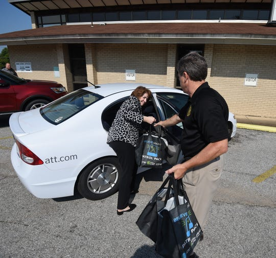 Cathy Foraker, director of external affairs for AT&T Arkansas, and Sheriff John Montgomery unload Patrol Pack food kits from the back of Foraker's car Thursday.
