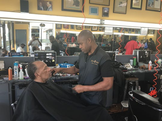 "Vladimir ""Boo-Man"" Averett, head barber and owner of Heritage Barbershop and ASU fan, cuts Donald Jones, a Tuskegee fan and alumni."