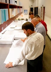 Workers with Caddell Construction look over plans for an upgrade to Bryant-Denny Stadium at the University of Alabama.