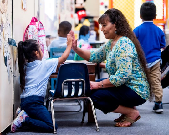 Brewbaker Primary School parent liaison Teresa Elmore, who is bilingual, gets a high five from a Spanish speaking student who was learning her way around on her first day at the school in Montgomery, Ala., on Thursday September 5, 2019.